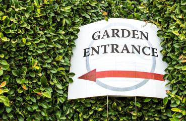 weathered cardboard sign surrounded by green hedges directing visitors to a garden entrance