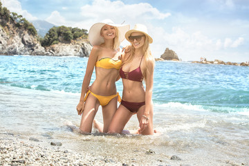 Two caucasian women having fun on the beach.