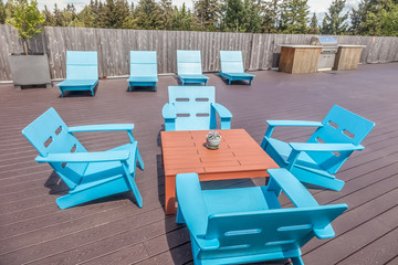 modern rooftop deck with blue plastic patio furniture