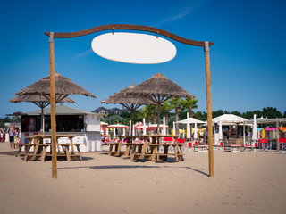 Wall Mural - Kiosk with straw umbrellas on the beachand white sign to use as copy space.