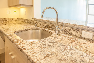 sleek modern high arc  faucet and brown marble counter