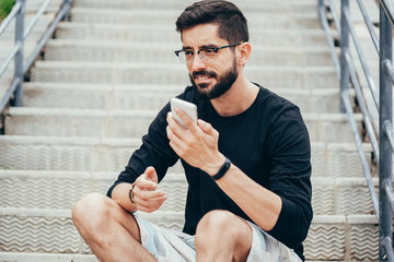 Leisure, technology, communication and people concept - young man using voice command recorder or calling on smartphone at street
