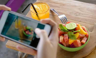 close up female hand with mobile phone screen taking picture of fruit salad and orange juice for sharing on internet social media app in healthy nutrition