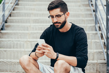 Handsome man with glasses holding cellphone and typing message on the street