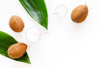 Tropical alcohol-free beverage. Fresh coconut milk in glasses with straw near coconut and palm leaves on white background top view copy space