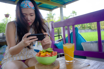 happy and pretty digital nomad Asian Korean girl taking picture of fruit salad with mobile phone for sharing on internet social media healthy nutrition