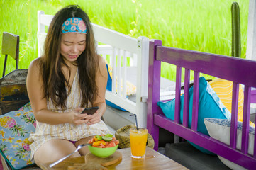 young happy and pretty digital nomad Asian Korean woman taking picture of fruit salad with mobile phone networking on internet social media