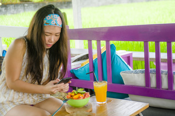 young happy and pretty digital nomad Asian Chinese girl taking picture of fruit salad with mobile phone networking on internet social media
