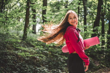 Beautiful young woman with fluttering hair with a fitness mat. Cropped image of a young athletic woman with fluttering hair in a sporty sweatshirt with a hood holding a sports mat on a forest path.