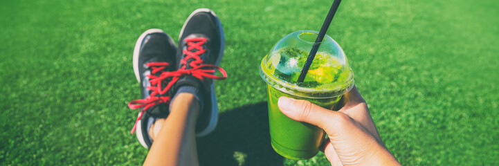 Healthy green smoothie detox juice woman holding drink shower running shoes in food selfie photo. Sport active lifestyle banner panorama.