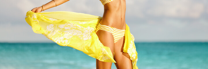 Bikini woman with yellow scarf unveiling toned slim thighs and body. Spa wellness free happy girl in bikini weight loss healthy living concept. Panorama banner.