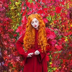 Young redhead sexy girl with very long curly hair in a red coat on a bright autumn background. A beautiful model with pale skin, red lips and closed eyes. Orange autumn leaves