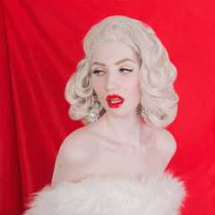 Beautiful blonde woman in a white fur coat on red background. Portrait of young unusual pale girl with white hair. Beautiful woman with a mole on her cheek and earrings on her ears