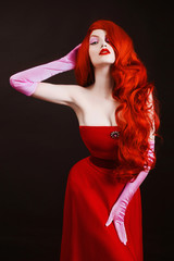 Young  redhead sexy girl with very long wavy hair in a red dress on a black background. A beautiful model with pale skin, red lips and blue eyes in pink gloves. Sexy slender figure