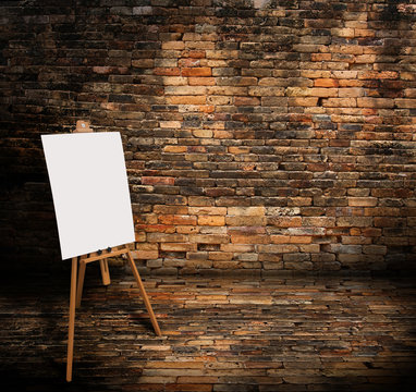 Wooden easel with mock up empty blank canvas stand in brick wall room