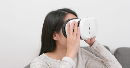 Woman looking with VR device at home