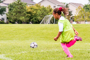 A young girl is learning how to play soccer