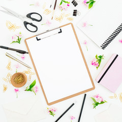 Education workspace composition with clipboard, notebook, flowers and accessories on white background. Flat lay, top view.