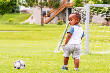 A little African toddler is playing soccer at summertime