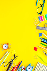 Education concept. Stationery for school pupil mockup with glasses and notebook on yellow background top view copy space