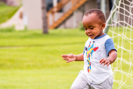 A close portrait of an African toddler enjoying a sunny day alone