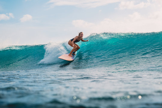 Surfer girl on surfboard. Surfer and wave