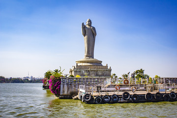 Sailing by the Giant Buddha Statue with Bright Pink Bougainvillea Plants in the Middle of Hussain Sagar Lake in Hyderabad, India Fototapete