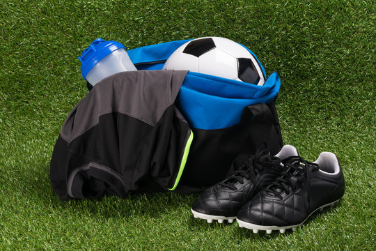 blue bag with a set for playing football on green grass