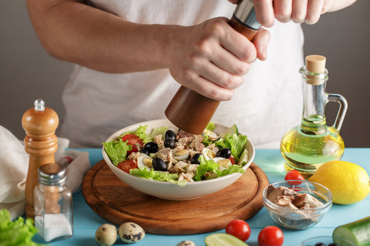 Chef seasoning tuna salad with pepper mill in the kitchen.