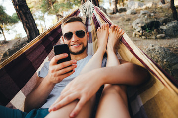 Time of laziness. A man is lying in a hammock and taking pictures of his girlfriend on the phone.