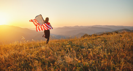 happy woman with flag of united states enjoying the sunset on nature.