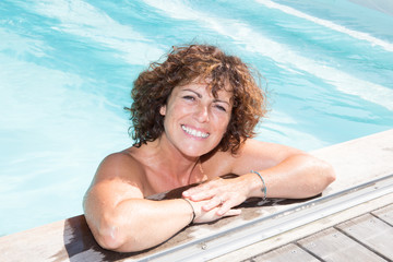 Latin tanned happy smiling woman enjoying the pool and looking at camera during summer vacation