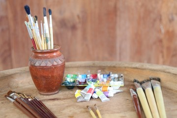 Paints and brushes on wooden background