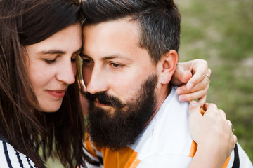 Dark haired couple of hipsters. A man with a beard.
