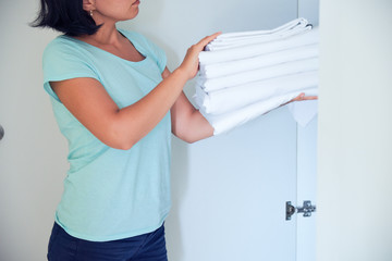 housewife holding a stack of washed bed linen. washing clothes and linen, bleaching of white things