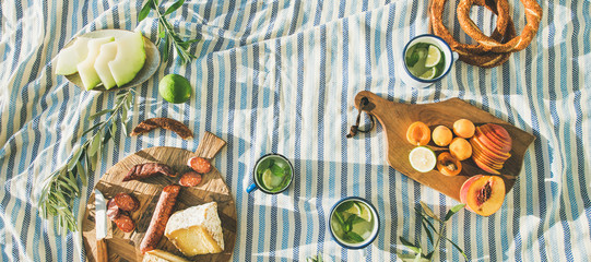 Flat-lay of summer picnic set with fruit, cheese, sausage, bagels and lemonade over striped blanket, top view, copy space