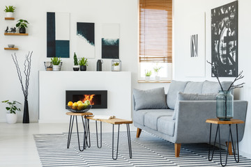 Real photo of a grey couch standing in front of a small wooden table in living room interior with a fireplace and posters on walls