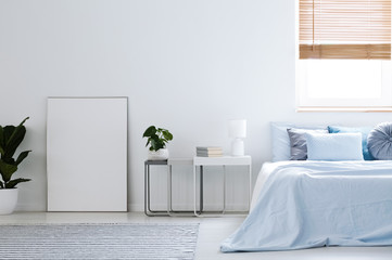 Mockup of white empty poster in simple hotel bedroom interior with blue bed. Real photo
