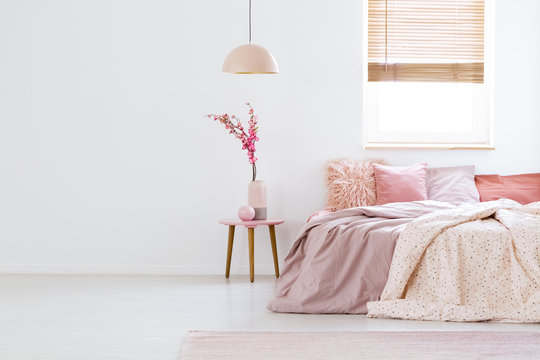 Lamp above table with flowers in pink pastel bedroom interior with window above bed. Real photo