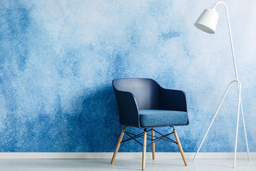 Modern dark blue chair and white metal lamp against ombre wall in a minimal style waiting room interior. Copy space. Real photo.