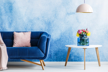 Comfortable plush settee with pastel cushion and a side table with fresh flowers in a vase against...