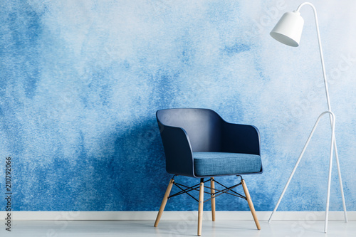 Modern Dark Blue Chair And White Metal Lamp Against Ombre Wall In A