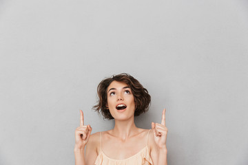 Portrait of a surprised young woman pointing fingers up