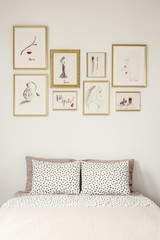 Stylish drawings gallery in golden frames above a cozy double bed with polka dot sheets in a white apartment room interior of a beauty lover