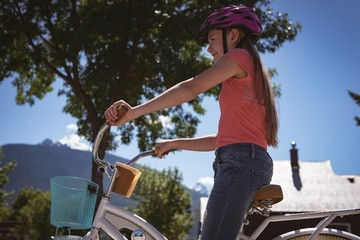 Smiling girl wearing helmet riding a bicycle