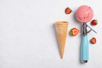 Ice cream strawberry taste scoop in spoon with waffle cone on white table background flatlay top view with copy space