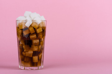 Drinking glass of of lump sugar cubes and soft cola drink on pink pastel background. Unhealthly diet with sweet sugary soft drinks concept.