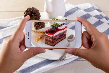 Photographing food concept - takes picture of cake with Smartphone