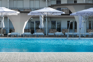 a pool with blue water and sunbeds with umbrellas in the background