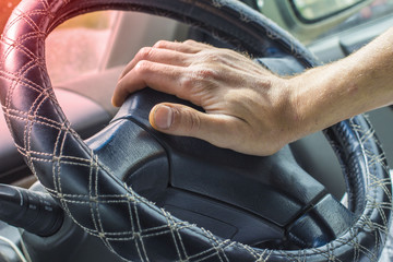 Male hand honking the car horn, man driving vehicle and beeping, front and back background blurred